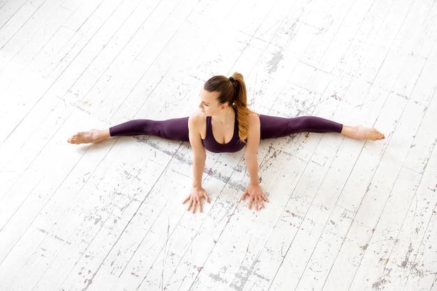 Молодая гимнастка делает фронтальную сплит-позу сверху вниз на белом полу в тренажерном зале с высоким ключом