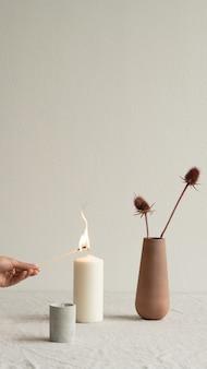 小さなセラミックガラスとテーブルの上に野生の花と茶色の粘土の花瓶の間に立っている白い芳香キャンドルを燃やす若い女性の手