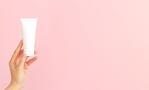 분홍색 배경에 빈 흰색 플라스틱 화장품 튜브를 들고 젊은 여성 손.