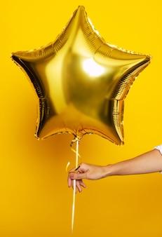 若い女性の手は黄色の背景に星の形をした明るい風船を持っています