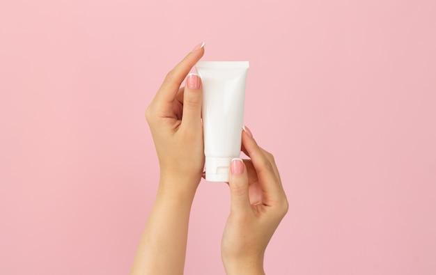 Молодые женские руки, держа пустую белую пластиковую косметическую трубку на розовом фоне.