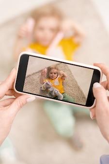 그녀의 사랑스러운 작은 아들이 거짓말을하고 바닥에 푹신한 깔개에 재미 스마트 폰이 비디오 또는 전화를 만드는 젊은 여성의 손