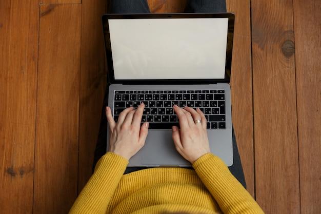 自宅で現代のラップトップに取り組んでいる若い女性の手。上面図