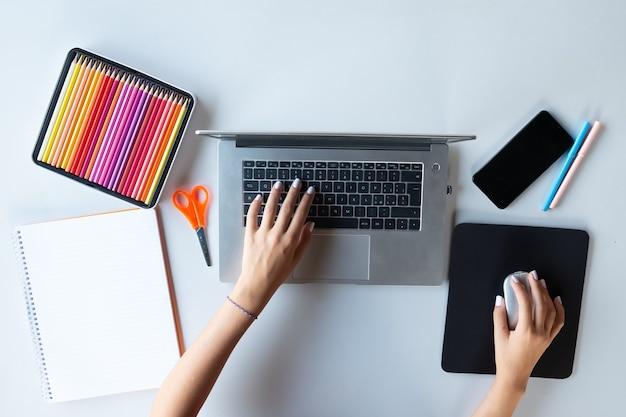 色はさみペンとマウスと机の上のラップトップで勉強している若い女性の手