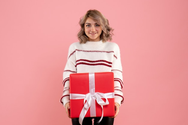 핑크에 크리스마스 선물을 행복 하 게 들고 젊은 여성