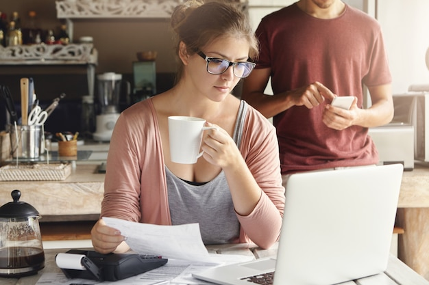 Young female having concentrated expression looking at screen of open laptop, holding paper and cup of coffee in her hands while calculating domestic expenses