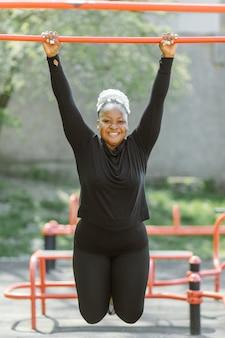 屋外でのトレーニングを楽しんでいる若い女性。スポーティな人々のライフスタイルのコンセプト。エクササイズをしているスポーツウェアの女性
