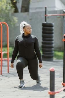 屋外でのトレーニングを楽しんでいる若い女性。スポーティな人々のライフスタイルのコンセプト。スクワットをしているスポーツウェアの女性。