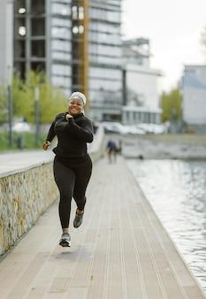 屋外でのトレーニングを楽しんでいる若い女性。スポーティな人々のライフスタイルのコンセプト。スポーツウェアのジョギングの女性