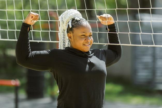屋外でのトレーニングを楽しんでいる若い女性。スポーティな人々のライフスタイルのコンセプト。バレーボールをしているスポーツウェアの女性