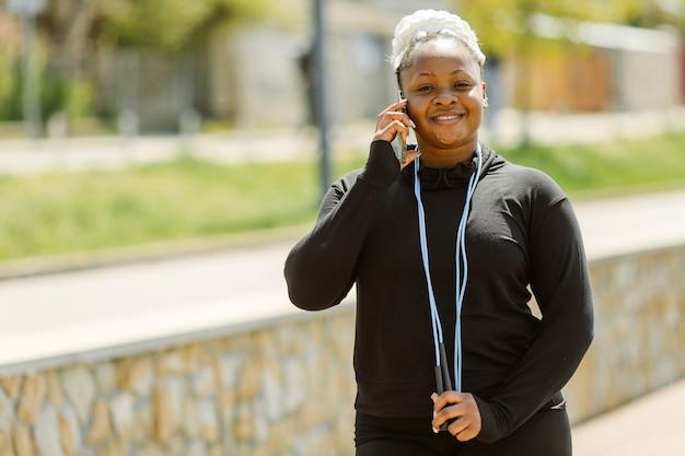 屋外でのトレーニングを楽しんでいる若い女性。スポーティな人々のライフスタイルのコンセプト。電話で話すスポーツウェアの女性