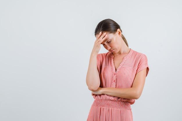 Молодая женщина, имеющая головную боль в полосатом платье и выглядящая усталой. передний план.