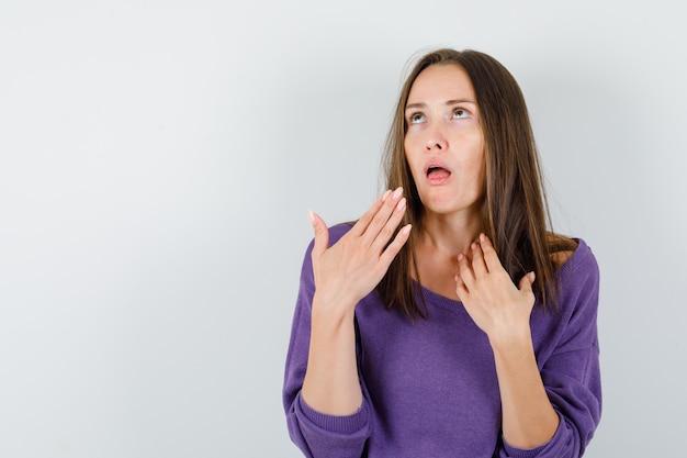 Giovane femmina che ha mal di gola in camicia viola e sembra amata. vista frontale.