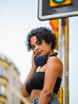 거리에서 헤드폰을 끼고 음악을 듣는 젊은 여성