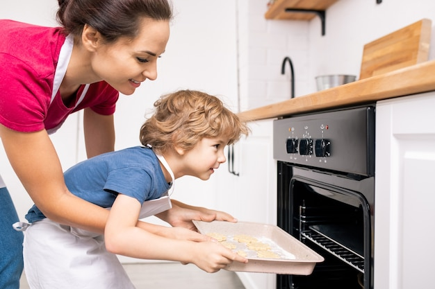 Young female helping her little son put tray with raw cookies into open oven while both bending forwards