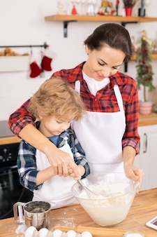 Young female helping her son whisk eggs with flour in bowl while preparing dough for tasty homemade cookies