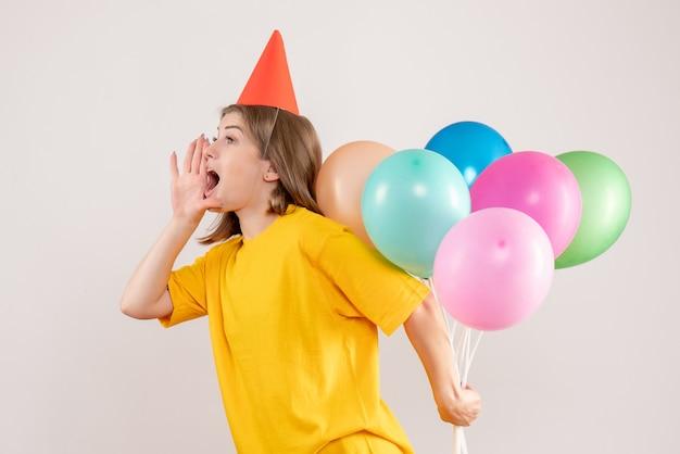 Молодая женщина прячет разноцветные воздушные шары за спиной, зовет белый