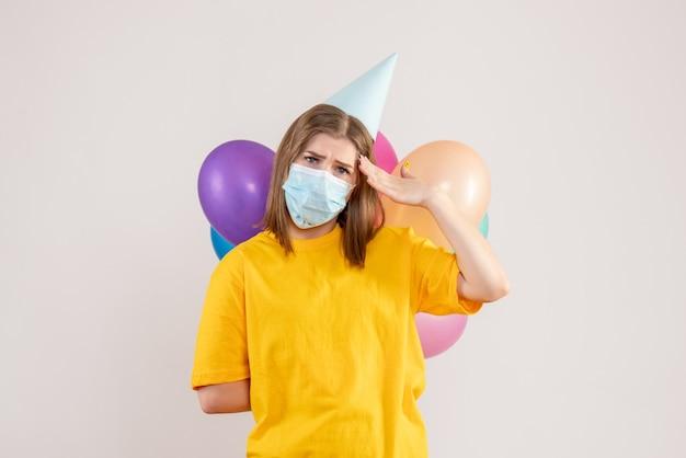 화이트 마스크에 그녀의 뒤에 다채로운 풍선을 숨기는 젊은 여성