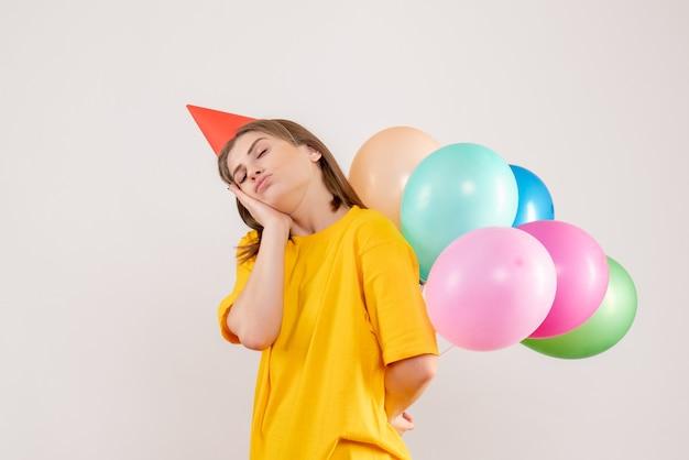 Молодая самка прячет за спиной разноцветные воздушные шары на белом