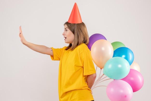 화이트에 그녀의 뒤의 뒤에 다채로운 풍선을 숨기는 젊은 여성