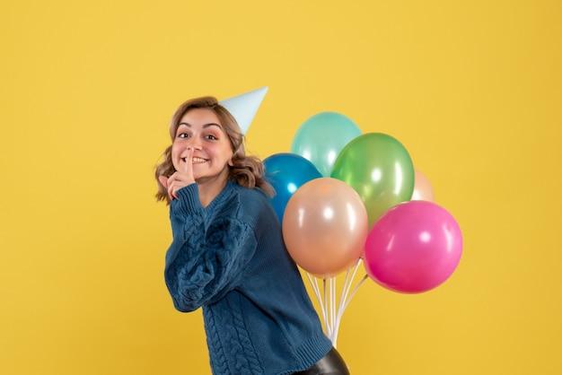 黄色の背中の後ろにカラフルな風船を隠す若い女性