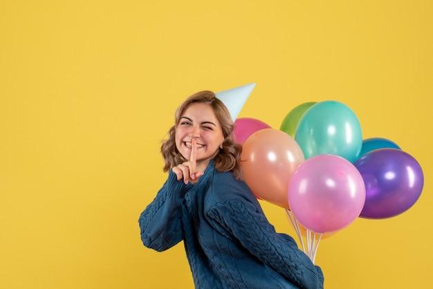 노란색에 그녀의 뒤에 다채로운 풍선을 숨기고 젊은 여성