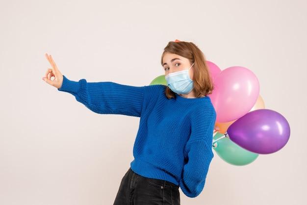 Giovane femmina nascondendo palloncini colorati dietro la schiena su bianco