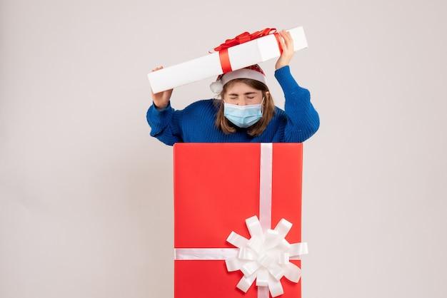 白のマスクでプレゼントボックスの中に隠れている若い女性