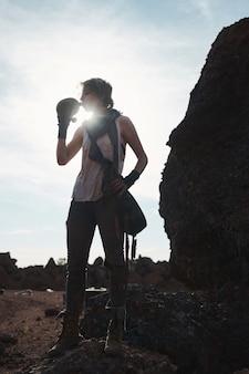 Молодая туристка пьет воду из бутылки, стоя на скале в горах
