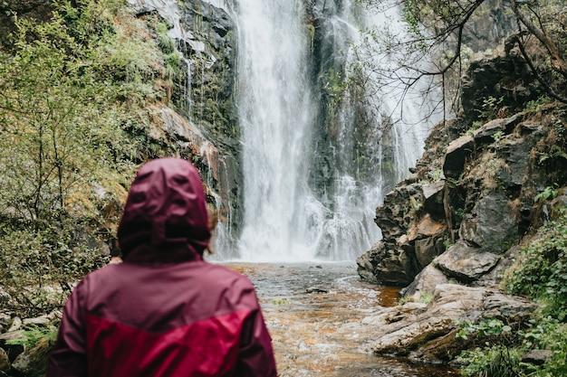 滝の前で若い女性ハイカー