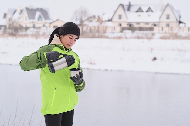 Молодая туристка в зеленой куртке стоит у озера и наливает горячий чай из термоса