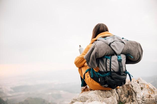 山を見下ろす水のボトルを保持している彼女のバックパックで若い女性ハイカー