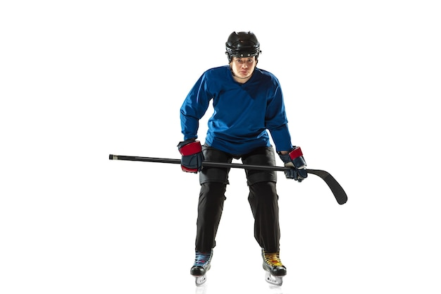 Young female hockey player with the stick on ice court and white background