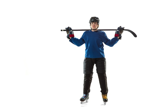 Young female hockey player with the stick on ice court and white wall. sportswoman wearing equipment and helmet posing. concept of sport, healthy lifestyle, motion, action, human emotions.