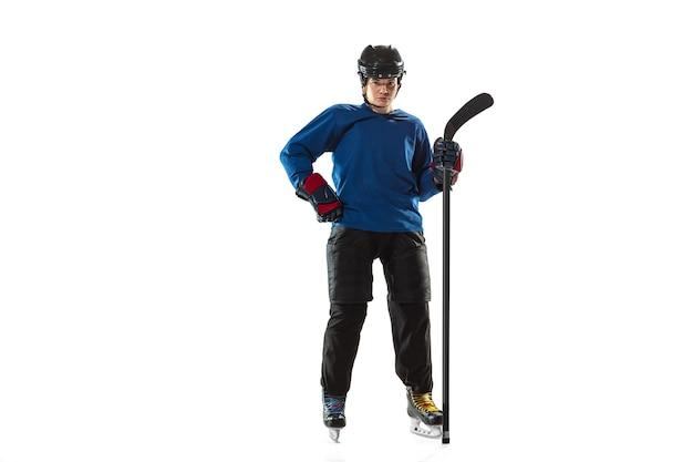 Giovane giocatore di hockey femminile con il bastone sul campo da ghiaccio e sul muro bianco. attrezzatura da portare sportiva e posa del casco. concetto di sport, stile di vita sano, movimento, azione, emozioni umane.