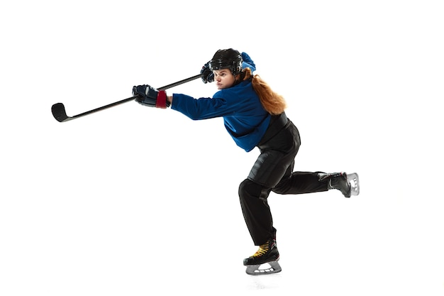 Young female hockey player with the stick on ice court and white wall. sportswoman wearing equipment and helmet training. concept of sport, healthy lifestyle, motion, action, human emotions.