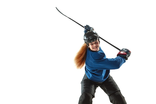 Young female hockey player with the stick on ice court and white wall