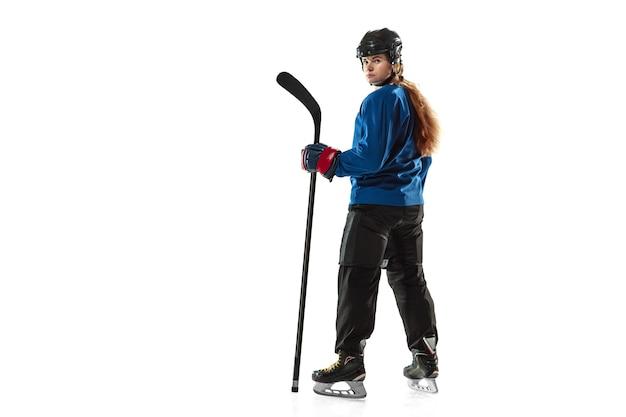 アイス コートと白い背景にスティックを持つ若い女性のホッケー選手