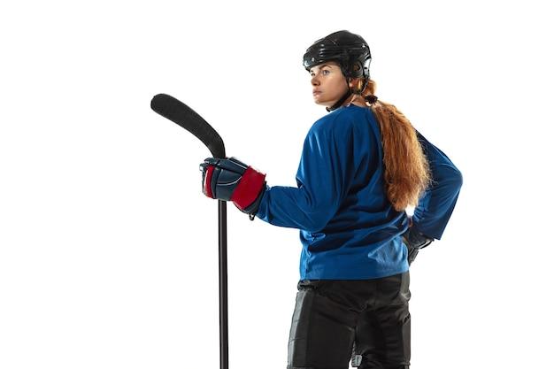 얼음 코트와 흰 벽에 막대기로 젊은 여성 하키 선수. sportswoman 장비 및 헬멧 포즈를 입고. 스포츠, 건강한 라이프 스타일, 모션, 액션, 인간 감정의 개념.