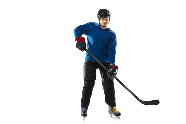 アイスコートと白い壁に棒で若い女性のホッケー選手。装備とヘルメットのトレーニングを身に着けているスポーツウーマン。スポーツ、健康的なライフスタイル、動き、行動、人間の感情の概念。