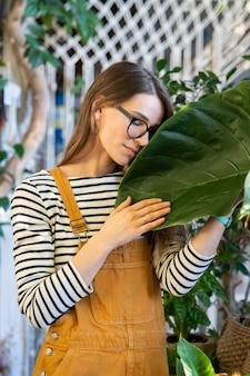 젊은 여성 온실이나 집 정원에서 퇴근 후 휴식 녹색 잎을 잡아