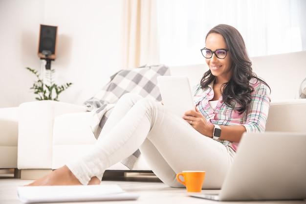 Молодая женщина держит планшет, улыбаясь, сидя на полу в гостиной. концепция домашнего офиса.