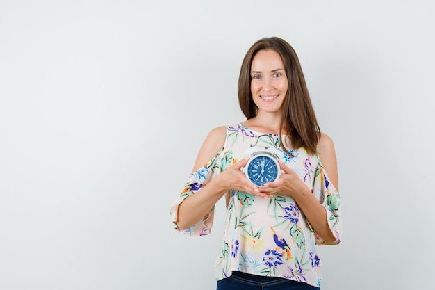 Young female holding alarm clock in shirt, jeans and looking cheery , front view.