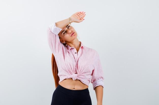カジュアルなシャツ、ズボンで額に腕を保持し、思慮深く見える若い女性