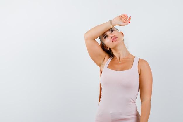 白いタンクトップの額に腕を保持し、疲れているように見える若い女性。正面図。