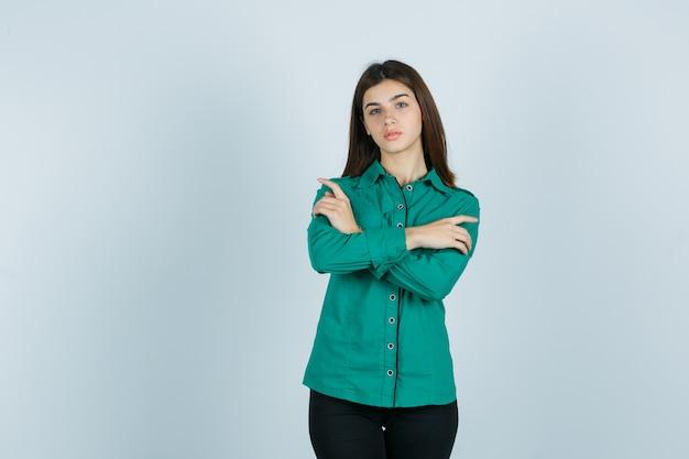 La giovane donna che tiene le braccia piegate in camicia verde e sembra interessata. vista frontale.