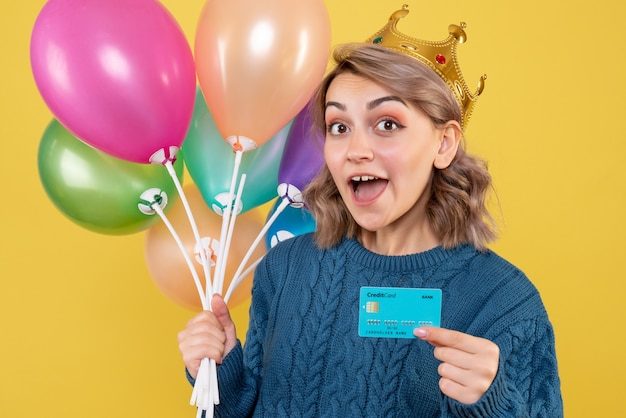 Young female holding balloons and bank card on yellow