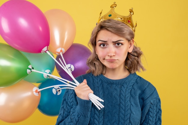 Young female holding balloons in crown on yellow