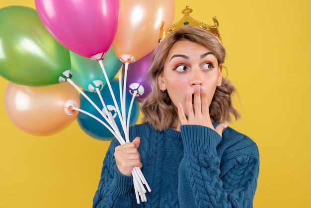 Giovane donna in possesso di palloncini in corona su giallo