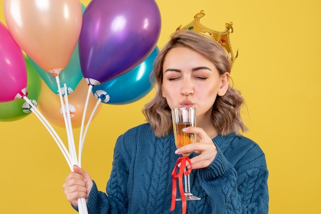 Young female holding balloons and glass of champagne on yellow